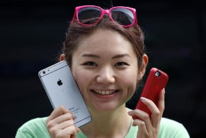 hone 6 plus and an iPhone 5s as she waits in a line, ahead of the September 19 release of iPhone 6 and iPhone 6 Plus, in front of an Apple Store at Tokyo's Ginza shopping district