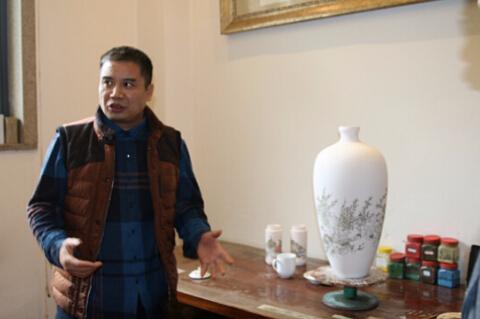 醴陵新世纪艺术馆馆长易龙华向记者介绍陶瓷设计流程,一旁的瓷胚是他的新作