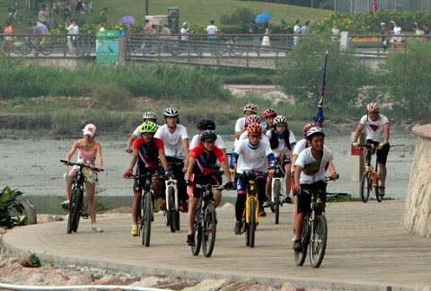 """(图为""""自行车骑士""""们在户外运动场面。--郑东升 摄)"""
