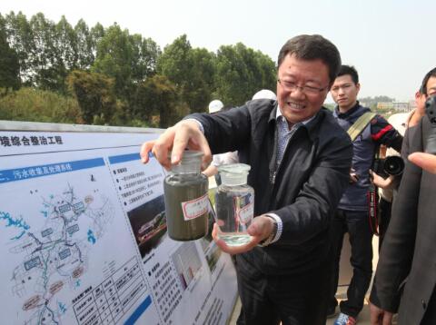 (环保人员向人大代表展示经处理的观澜河水。许业周 摄)